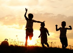 Silhouettes of children as they play against the setting sun.